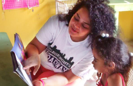 Nicol reads with Yale service-learning trip volunteer Anabelle